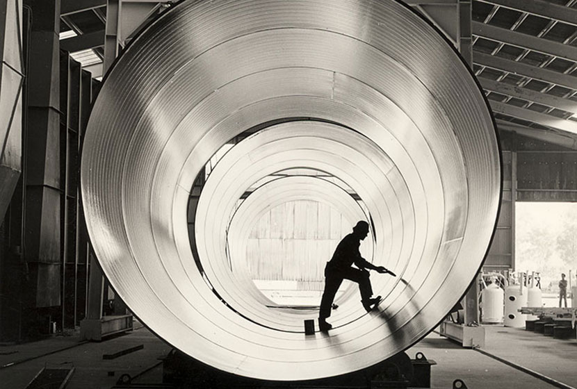 Zincline worker preparing large pipe sections before the galvanising process.