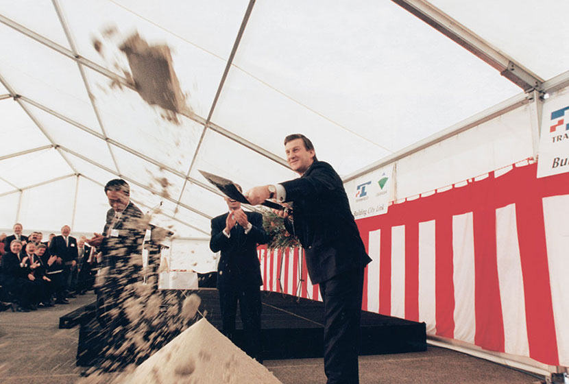 Premier Jeff Kennett throws sand to the media to mark the commencement of construction, 29 May 1996.